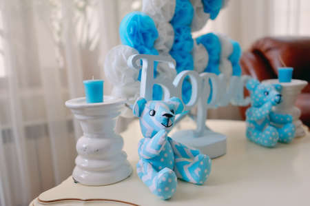 festive decoration in blue and white colors of paper flowers, candles and toy bear photo