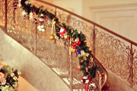 staircase with metal railing decoration Christmas garland of pine and toys photo
