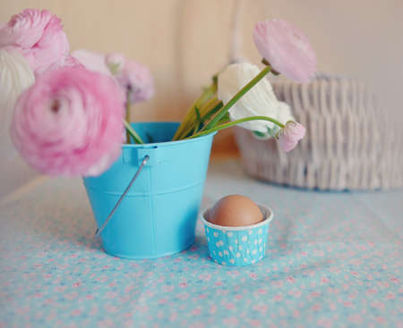 beautiful and delicate bouquet of buttercups in a blue bucket and egg in a basket photo