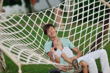 a summer day on the nature of the father and son rest in the big white hammock