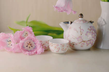 festive still life on a light background pink tulips and tea service photo