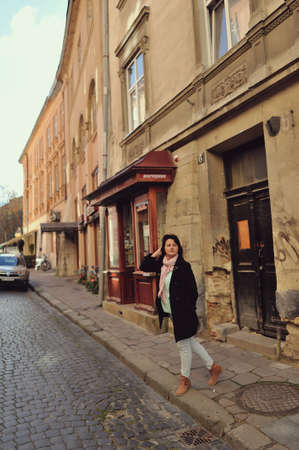 on the street of the old town near the road a woman in a black coat and trousers