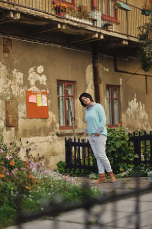 woman in jeans and boots and an old house with a front garden photo