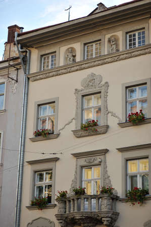 old house with windows and balcony railings metal flowerpots with flowers photo