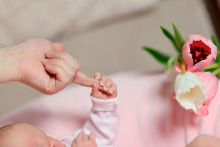 Baby hand holding mother finger on a gentle background with pink tulips photo