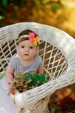 summer vacation at a table in the garden with berries sitting in a wicker chair cute little girl with a flower on her head photo