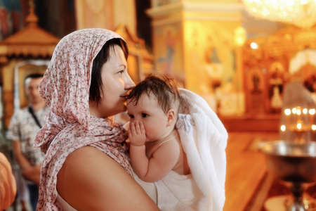 in the church against the icons and lights woman holding a cute baby in her arms photo