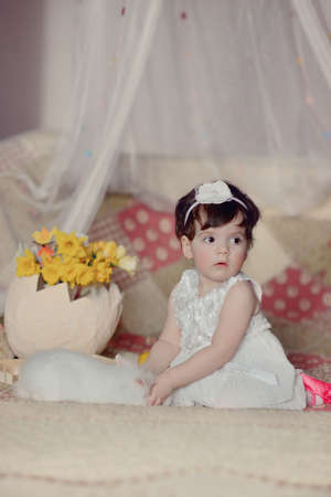 little girl in a beautiful white dress with bunny, flowers and lemons photo