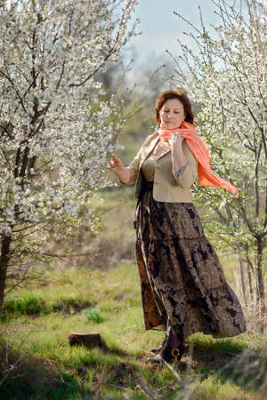 long skirt: in the garden with flowering trees posing woman with a scarf in a long skirt Stock Photo
