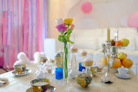 tea candles:  Holiday tea party and white table with beautiful tableware and decorations