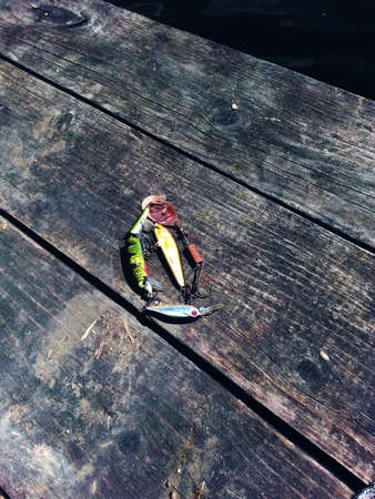 on a wooden bridge is fishing tackle as colored fish photo