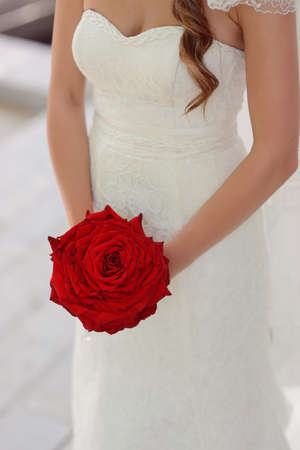 Bride In White Dress Holding A Big Red Rose Photo