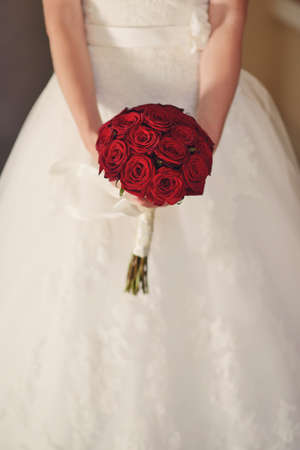 in white wedding dress the bride holding a bouquet of red roses