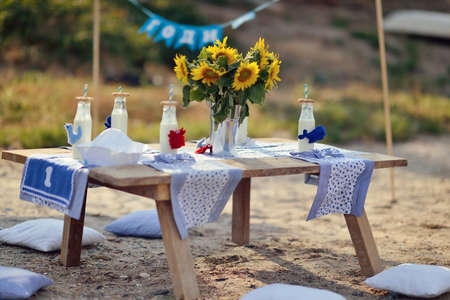 Outdoor wooden table with a bottle of milk and a vase with sunflowers
