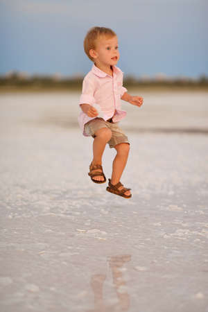 little boy jumping with joy on the face of a summer day on the nature of the water