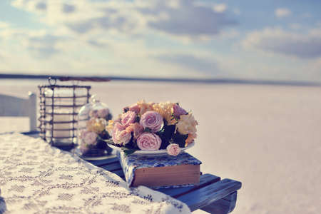 composition on the background of the horizon on a wooden table wicker basket and a flask with a bouquet of roses