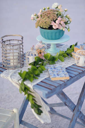 composition on a wooden table wicker basket and a vase bouquet of pink flowers and a book photo