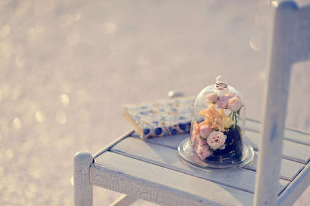on a white wooden chair decorative bulb with a bouquet of roses and a book