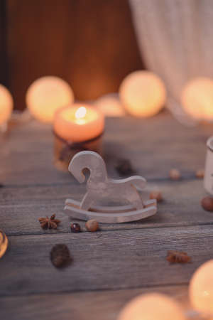 on wooden table lit candle and garland and wooden horses