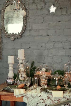 velas de navidad: mesa con adornos navideños y grandes velas blancas, cristalería, conos verdes rama de árbol