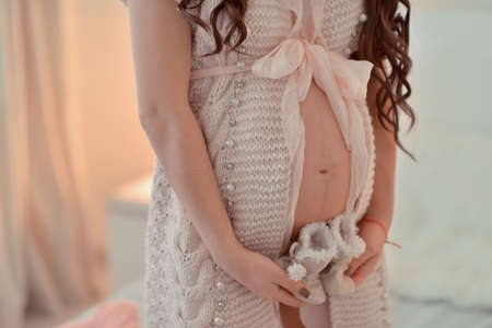 knitted jacket: pregnant woman in a knitted jacket with a bow in his hands holding baby boots