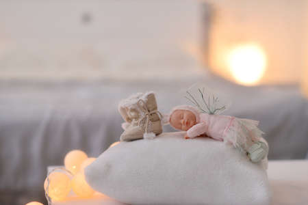 lit garland baby fur boots and sleeping doll on light background