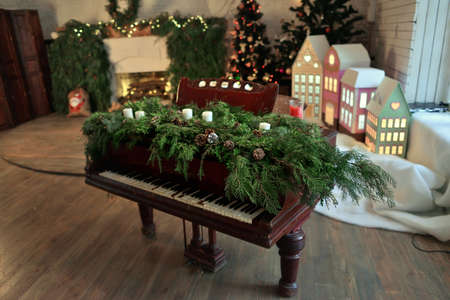 a room with a fireplace and Christmas decorations a piano decorated with green branches with cones and candles
