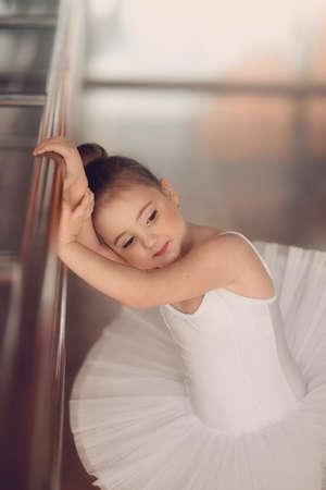 in the hall near the handrail Ballet Bars little ballerina in white tutu
