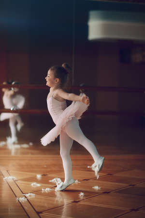 in the hall near the large mirrors dancing little ballerina in white tutu photo