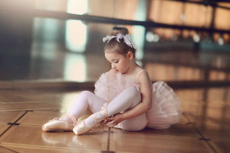 in the hall on the background of large mirrors on the floor sits a little ballerina in white tutu Stock Photo