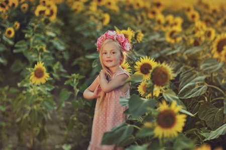 little girl with long hair in a pink dress and a wreath on his head in the sunflowers photo