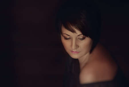 on a dark background portrait of a girl with beautiful makeup and stylish haircut photo