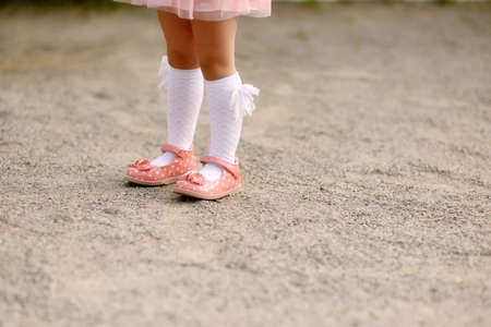 Childrens feet in white socks and pink shoes photo