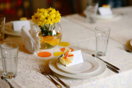 white plates on a table with a fork and knife vase with yellow flowers photo