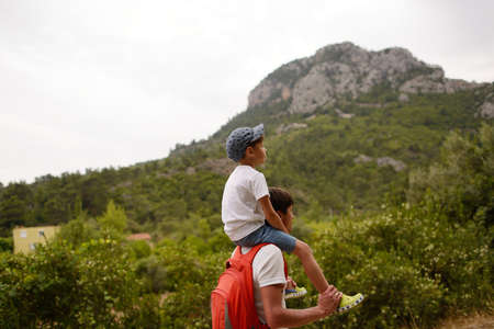 father with a backpack and a son on a walk in the mountains photo