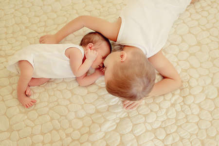 1 2 years: on the bed are two cute little brother, the baby sleeps Stock Photo
