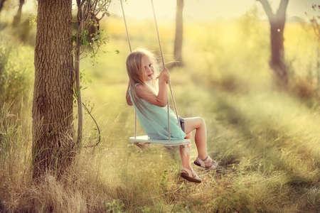 petite fille avec robe: dans le parc près les grands arbres monter sur une balançoire Jolie fille aux cheveux longs Banque d'images