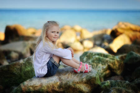 by the sea on the rocks sits a little girl with white long hair photo