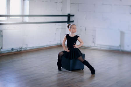 teen feet: little ballerina in a black dress in pantyhose sitting on a black square in the hall