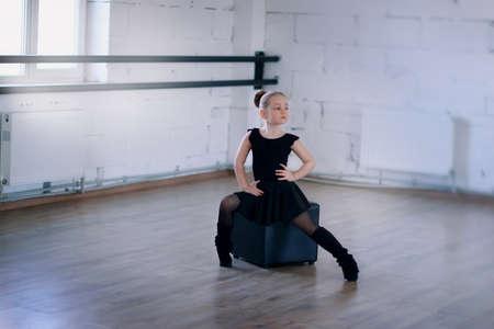 pies bailando: pequeña bailarina en un vestido negro en medias sentado en un cuadrado negro en la sala