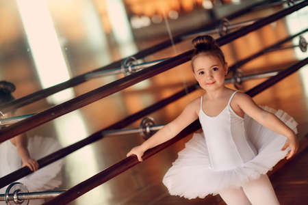in the hall near the large mirrors dancing little ballerina in white tutu