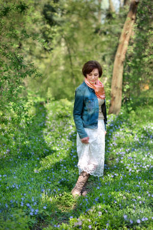 denim jacket: in the park woman in a denim jacket on the field with blue flowers