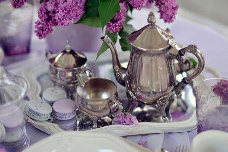 銀食器とテーブルの上のライラックの花束花瓶