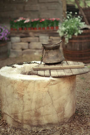 in the courtyard on the background of flowers and barrels round the well with a bucket Stock fotó