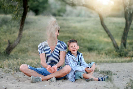 striped vest: at sunset on the nature of the father in the striped vest with a young son playing with sand Stock Photo