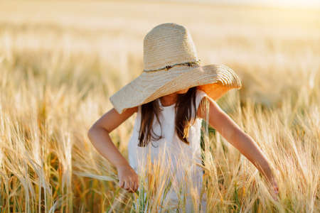 cropland: little girl in a straw hat and with long hair on a field of wheat