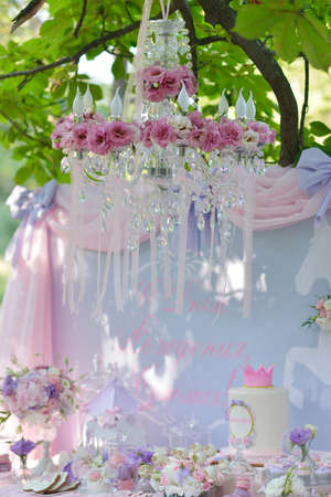 weighs: on a tree with green leaves weighs chandelier with bouquets of flowers and ribbons