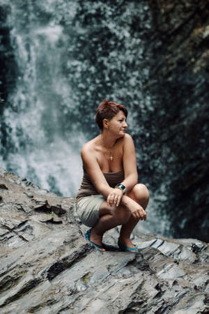 large rock: Against the of a waterfall on a large rock sitting woman
