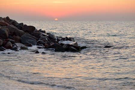 beautiful sunrise over the sea, surf and rock