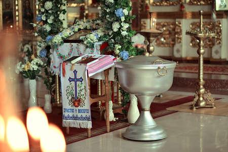 pila bautismal: en el templo de la decoración festiva con flores y velas en una fuente grande
